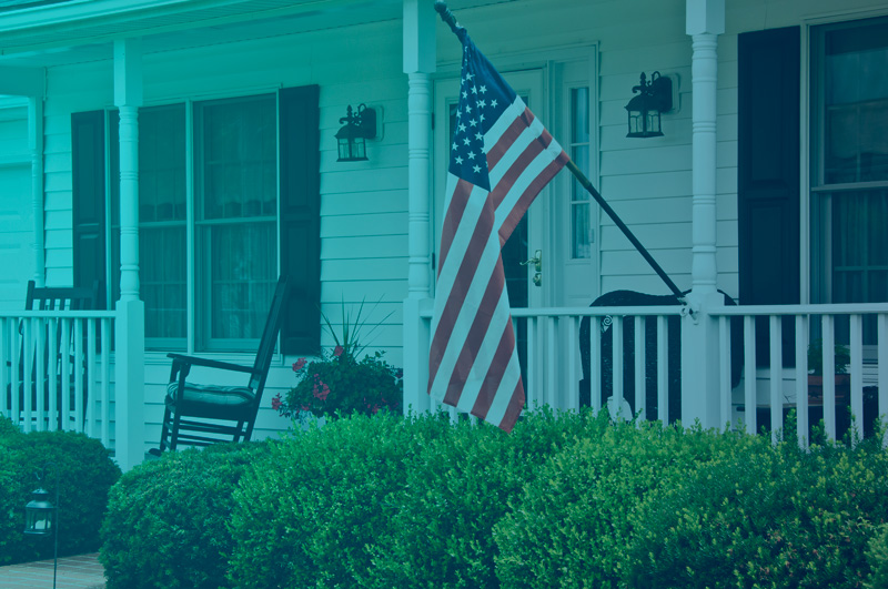 Front porch of house with American flag flying